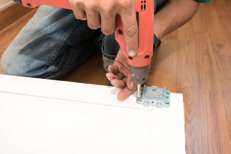 assemble: carpenter using Screwdriver assemble furniture Stock Photo