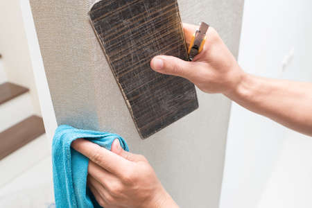 putting up: Handyman putting up wallpaper on the white walls Stock Photo