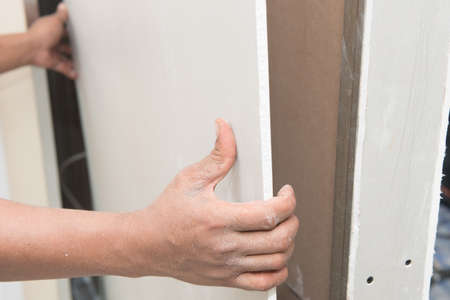 plasterboard: Construction worker holding gypsum board