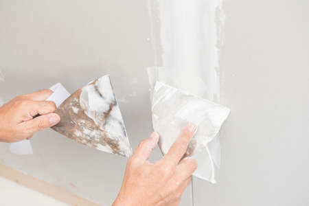 plaster board: Hand of worker with plaster and trowel to gypsum board