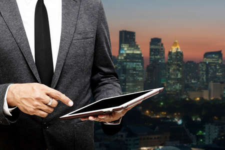 personal point of view: business man holding computer tablet selective focus on pointing finger with city light background Stock Photo
