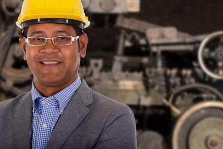 yellow helmet: male engineer wear yellow helmet with machine in background Stock Photo