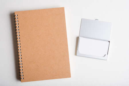 bussiness man: blank name card in case and blank note book on wooden table
