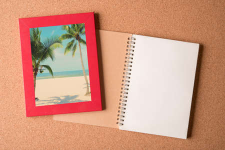 note pad: note book and picture of beach in the frame on wooden table Stock Photo
