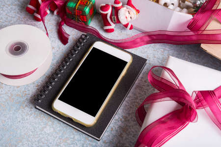 blank smart phone and holiday decoration on wood table