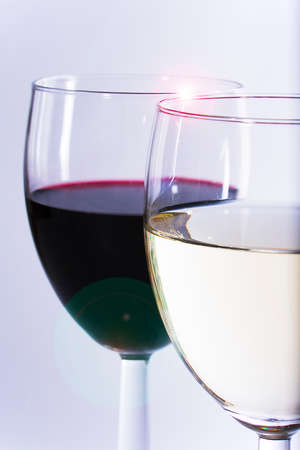 socialise: Red and white wine in pair of wine glasses on plain