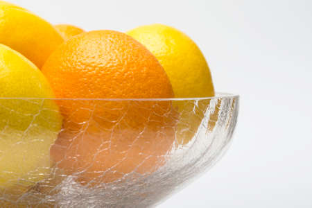 Oranges and lemons in glass bowl, high key on white photo