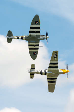 Duxford, UK - 25th May 2014: Vintage  fighters, British Supermarine Spitfire, with US P51 Mustang at Duxford Airshow.