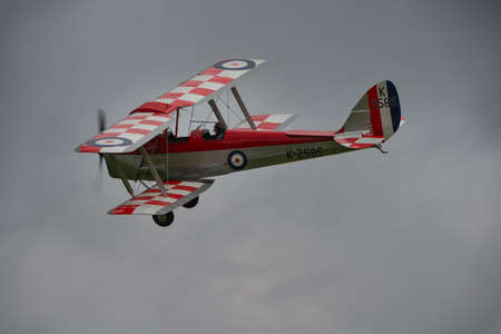 Biggleswade, UK - 29 June 2014: A vintage DH82a Tiger Moth biplane in flight at the Shuttleworth Collection air show.