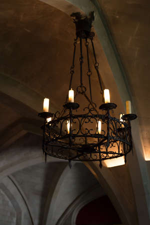 Old candelabra in vaulted roof Stock Photo