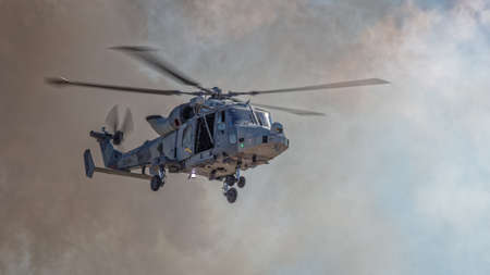 YEOVILTON, UK - 7th July 2018:  Royal Navy   helicopter in flight above pyrotechnic display simulating an attack at Yeovilton  airfield in south western UK Editöryel
