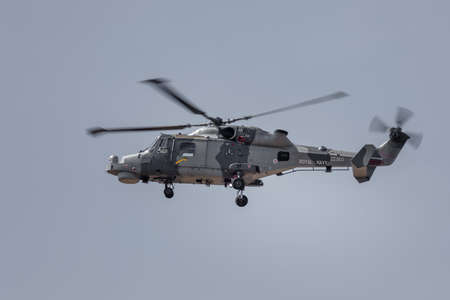 YEOVILTON, UK - 7th July 2018: A Royal Navy Lynx HMA.8  helicopter in flight over Yeovilton RNAS airfield in south western UK