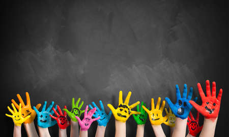 painted hands in front of a blackboard Stock Photo