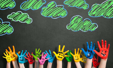 colorful hands in front of a chalkboard with clouds photo