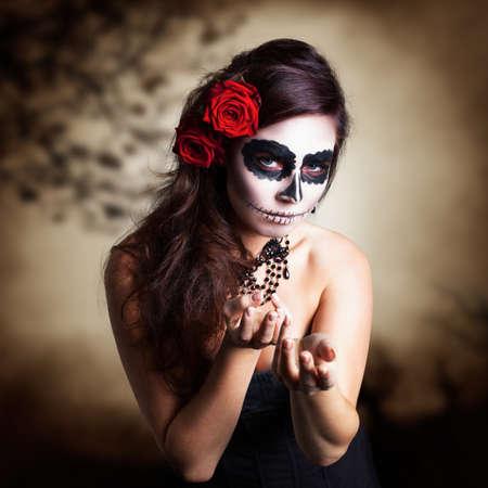 Mujer joven y atractiva con maquillaje del cráneo del azúcar