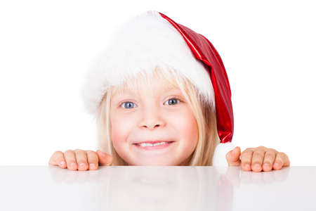 young girl with christmas hat looking over a table photo