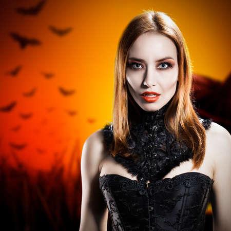 vampire bats: attractive vampire in front of a halloween background