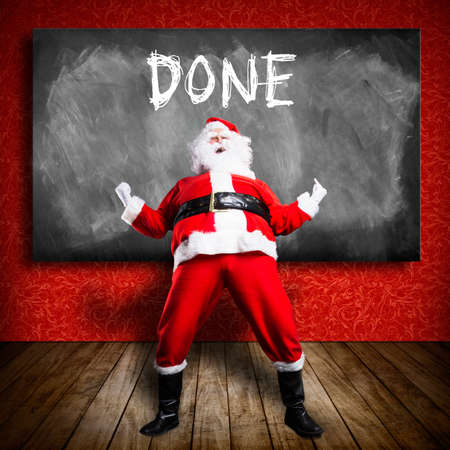 happy Santa Claus in front of a blackboard with the text done photo