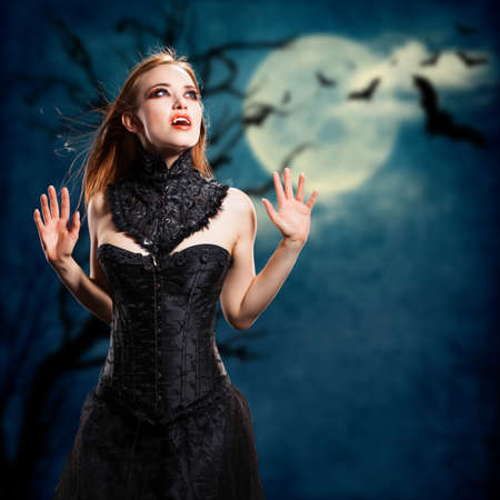 affliction: attractive vampire in front of a dark landscape with full moon and flying bats