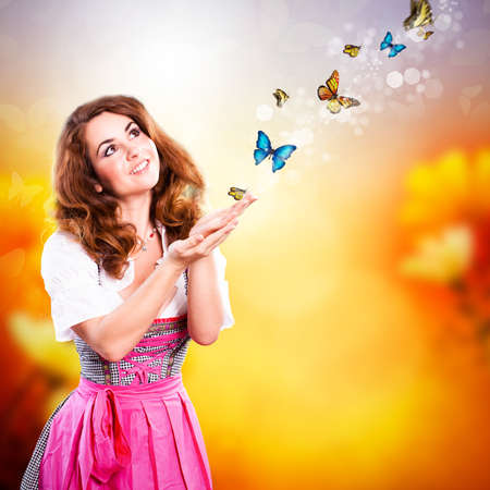 attractive young girl in a dirndl with butterflies photo
