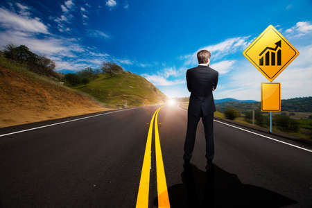 difficult journey: businessman standing in front of a sign with a chart on a windy road