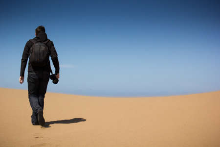 man alone: young man with a camera on a dune