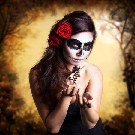 traje mexicano: Mujer joven y atractiva con maquillaje calavera de azúcar y decoración del pelo hecho con rosas