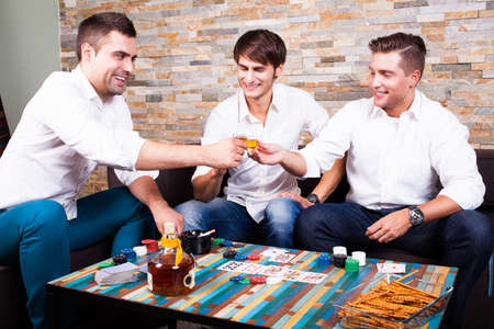 drinks after work: friends playing poker and drinking rum shots