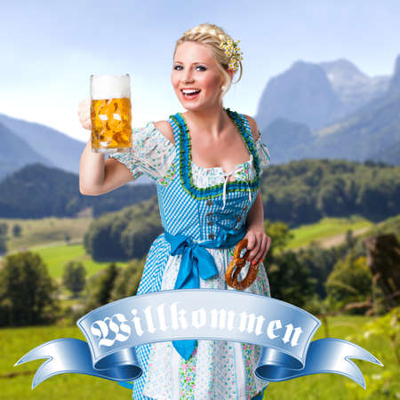 tracht: attractive young girl in a dirndl with a beer and a badge stating welcome in German