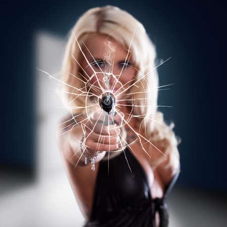 mujer con pistola: Mujer disparando una pistola a través de una ventana