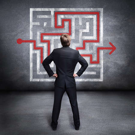 solved: businessman standing in front of a maze with a solution