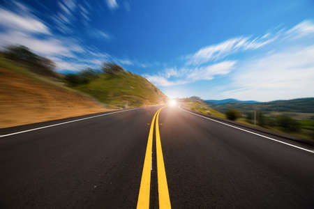 road with a light at the end symbolizing future and speed photo