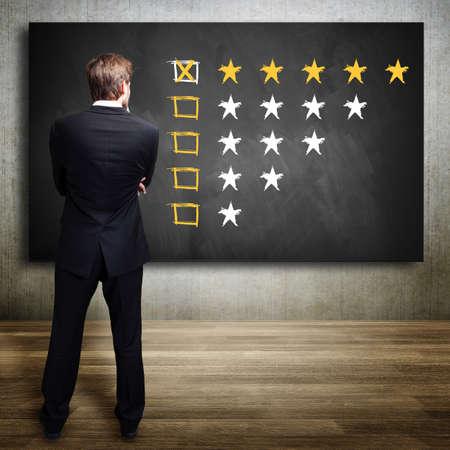 compromiso: hombre de negocios mirando una calificaci�n de cinco estrellas