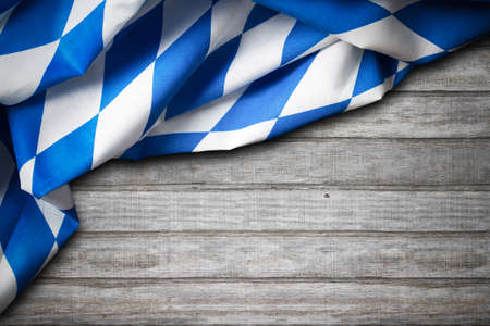 oktoberfest background: bavarian table cloth on a wooden table