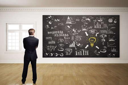 empezar: hombre de negocios de pie delante de una pizarra con muchos diagramas