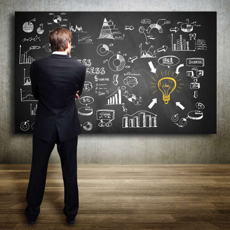 businessman standing in front of a blackboard with many diagrams