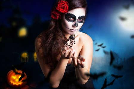 Mujer con estilo del cráneo del azúcar en frente de un fondo de halloween