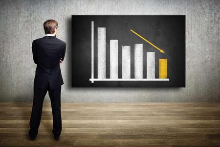 Geschäftsmann, der ein Diagramm, das eine rückläufige Grafik