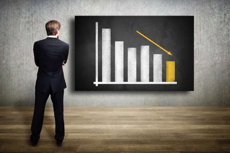 businessman looking at a diagram showing a declining graph