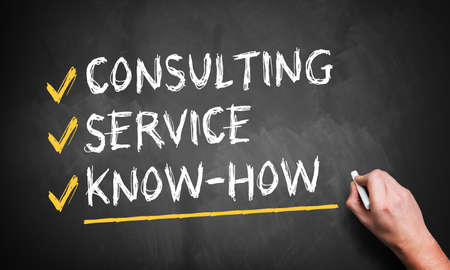 man writing consulting, service, know how on a blackboard  photo