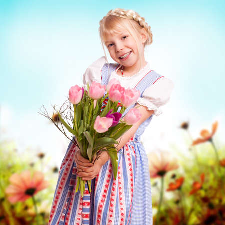 happy young girl in a dirndl with a bouquet of flowers  photo