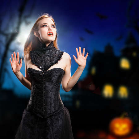 sexy vampire in front of a halloween house  photo