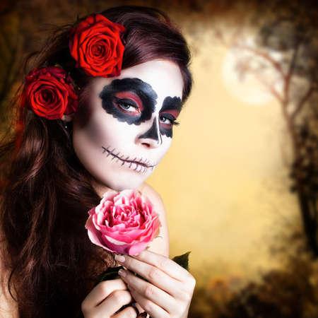 traje mexicano: Mujer joven y atractiva con maquillaje calavera de azúcar y una rosa en la mano