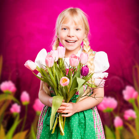 dirndl dress: happy young girl in a dirndl with a bouquet of flowers  Stock Photo