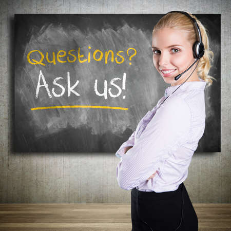 personal assistant: businesswoman with headset and a blackboard stating \\\Questions? Ask us\\\