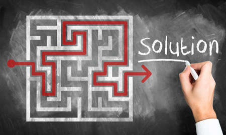 solved maze puzzle: Man sketching a solution through a maze on a chalkboard