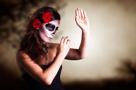 attractive young woman with sugar skull makeup photo