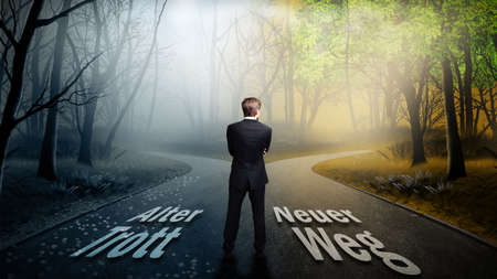 new way: man standing on a crossroad with the signs old routine to the left and new way to the right Stock Photo
