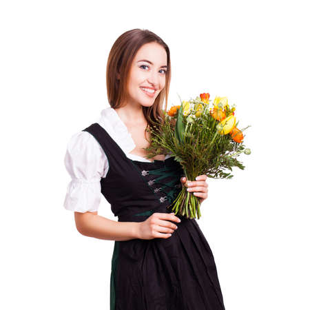 tracht: attractive young woman in a dirndl with a bouquet of tulips