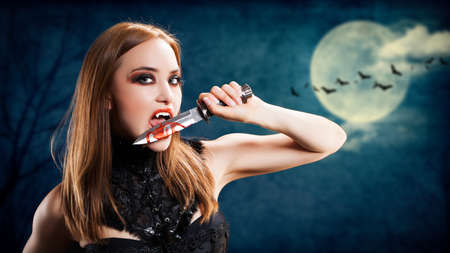 dracula woman: attractive vampire with a bloody knife